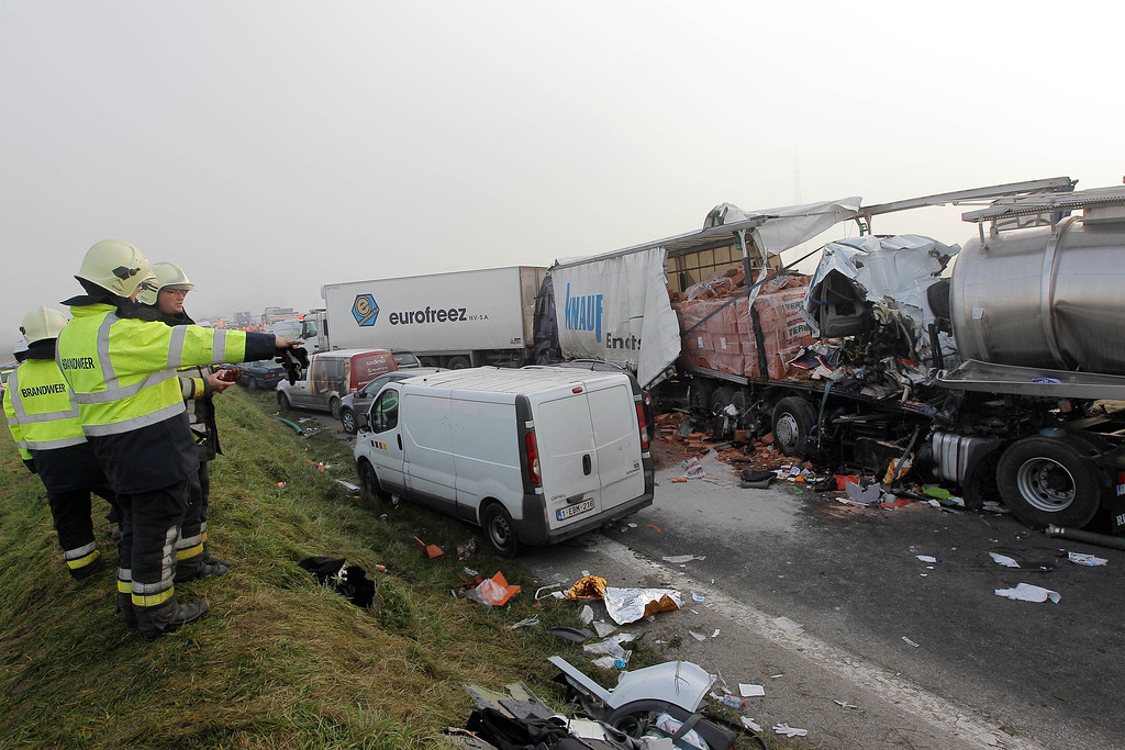 . Firefighters stand on top of a shoulder looking at the damage of a giant car crash on the A19 highway in Zonnebeke, western Belgium, Tuesday, Dec. 3, 2013.  (AP Photo/Yves Logghe)