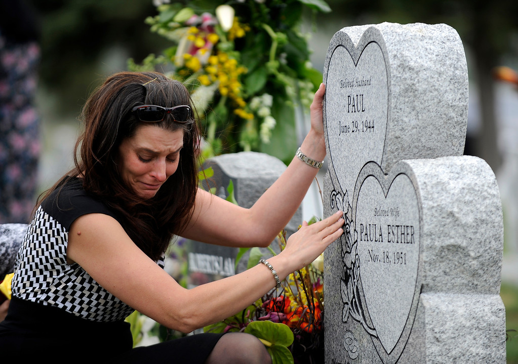 . Andrea Sandoval Reed, grieves at her father\'s headstone at Mt. Olivet Cemetery during burial services. Andrea\'s father, Paul Sandoval, a former Colorado State Senator, passed away April 24th, 2012 after a battle with pancreatic cancer. Andy Cross, The Denver Post