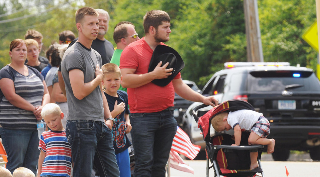 . From left: Tim Pedersen of Elk River, Minn., his son Dylan, 8, and brother-in-law Joel Carlson of Lake Norden, S.D. pay their respects as officer Patrick\'s processional passes in Dodd Road. Climbing out of his stroller is Eli Murney, 2. (Pioneer Press: Scott Takushi)