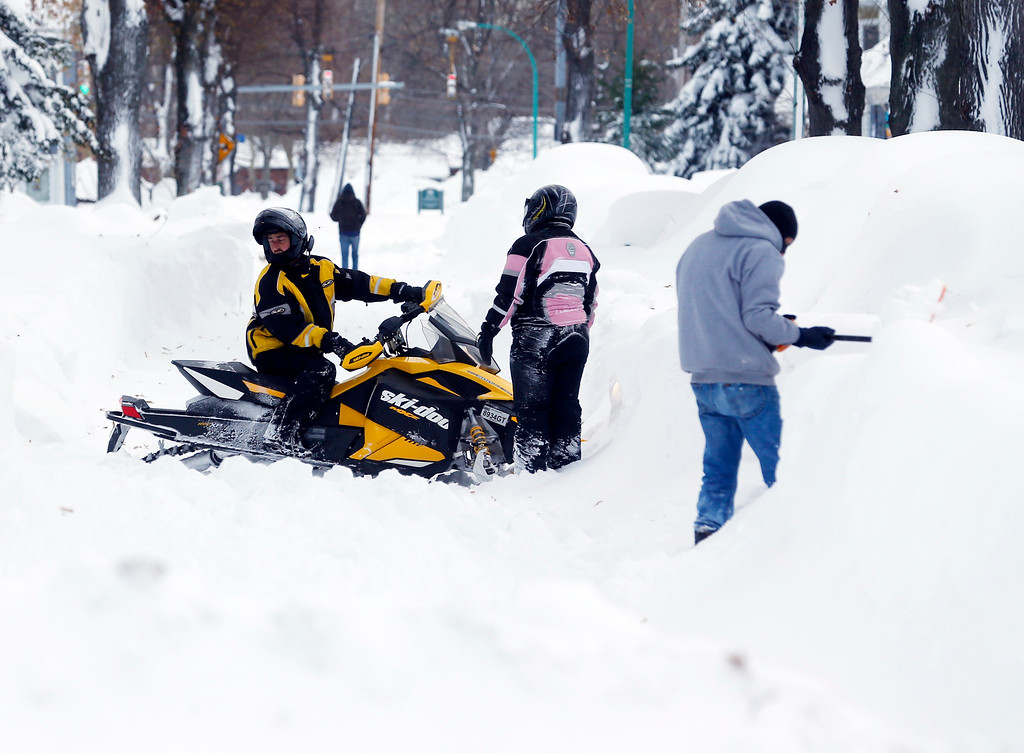 . A snowmobile is forced to turn around on a snow-clogged street in the south Buffalo area on Thursday, Nov. 20, 2014, in Buffalo, N.Y.  A new blast of lake-effect snow pounded Buffalo for a third day piling more misery on a city already buried by an epic, deadly snowfall that could leave some areas with nearly 8 feet of snow on the ground when it\'s all done. (AP Photo/Mike Groll)
