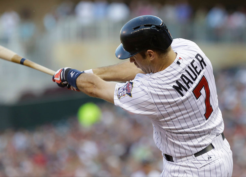 . Minnesota Twins\' Joe Mauer  swings on an RBI single off New York Yankees pitcher Phil Hughes in the third inning of a baseball game, Tuesday, July 2, 2013 in Minneapolis. (AP Photo/Jim Mone)