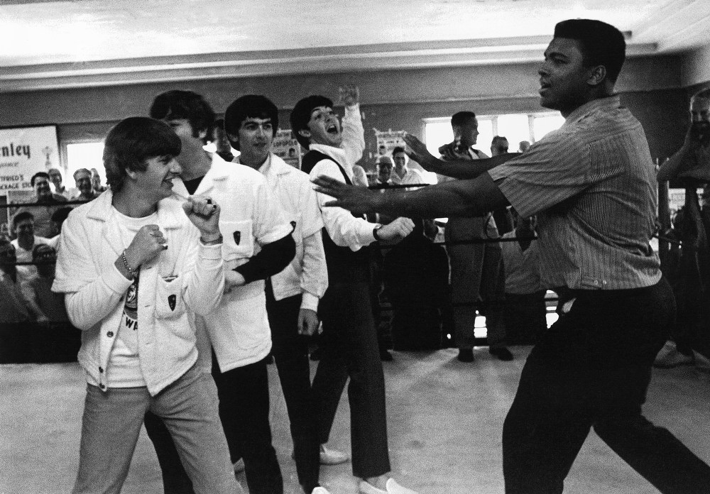 Description of . Muhammad Ali, who'll fight heavyweight champ Sonny Liston on February 25, clowns a bit with the Beatles at his training camp in Miami Beach, Florida on Tuesday, Feb. 18, 1964.   The Beatles are, from left: Ringo Starr, John Lennon, George Harrison, and Paul McCartney. (AP Photo)
