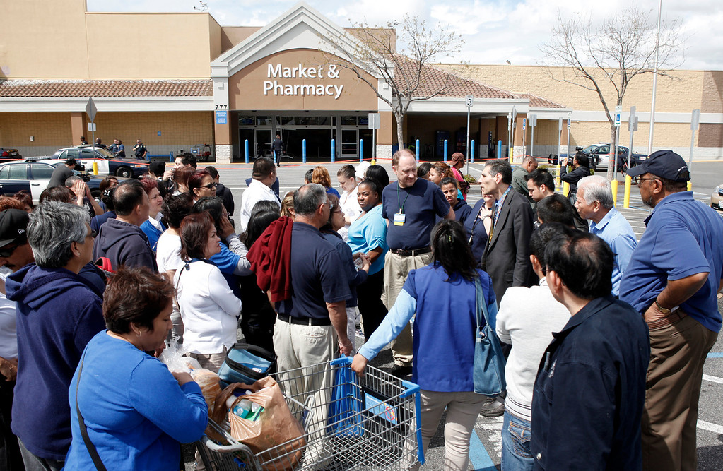 . Walmart employees huddle around for word about one of their colleagues injured in an incident where a red Cutlass Salon was driven into the business on Story Road in San Jose, Calif., Sunday afternoon March 31, 2013. (Karl Mondon/Staff)