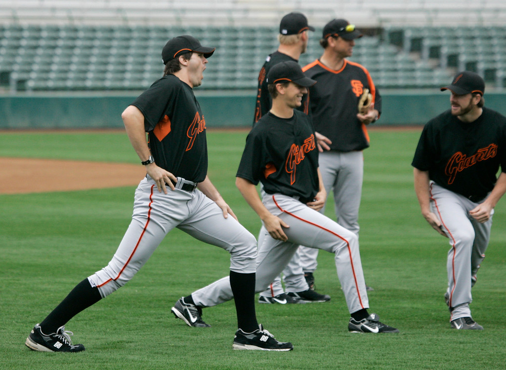 . San Francisco Giants\' pitcher Barry Zito, left, yawns while stretching with pitchers Patrick Misch, center, and Brian Wilson, right, during their spring training baseball workout in Scottsdale, Ariz., Monday, Feb. 19, 2007.  (AP Photo/Eric Risberg)