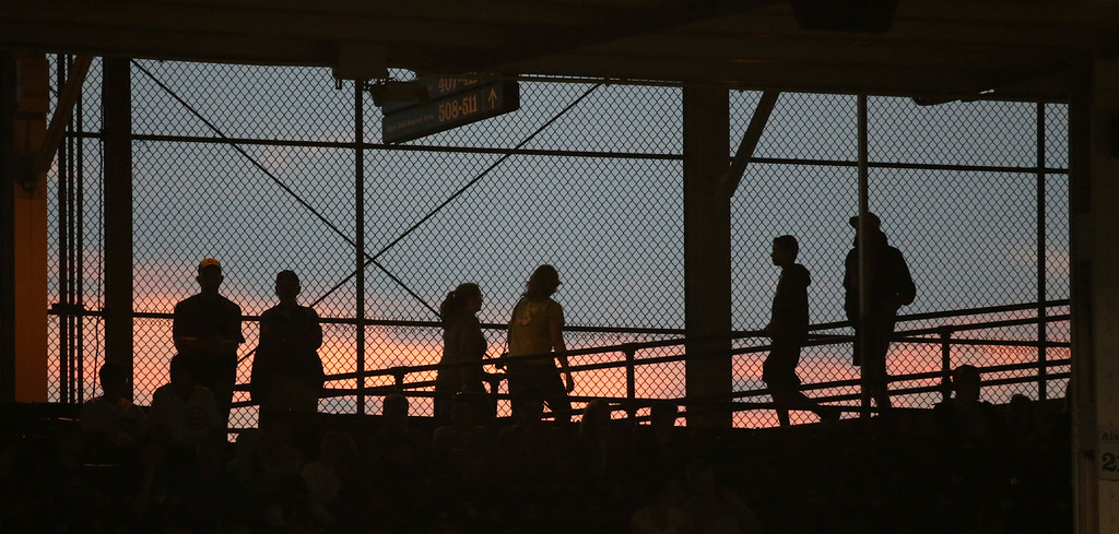 . Fans are silhouetted as they watch a baseball game between the Chicago Cubs and the Colorado Rockies, as the sun sets in the West, Tuesday, July 29, 2014, in Chicago. (AP Photo/Charles Rex Arbogast)