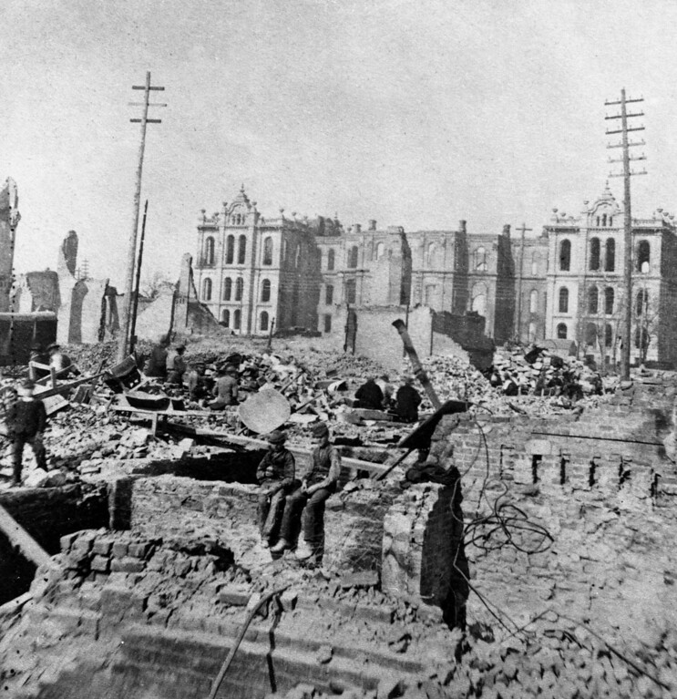 . Two boys sit on top of a partial stone wall in the wreckage of a burned-out building at Madison and Clark Streets, with the Court House in the background following the great Chicago fire of October 8 - 10, 1871, Chicago, Illinois. (Photo by Hulton|Archive/Getty Images)
