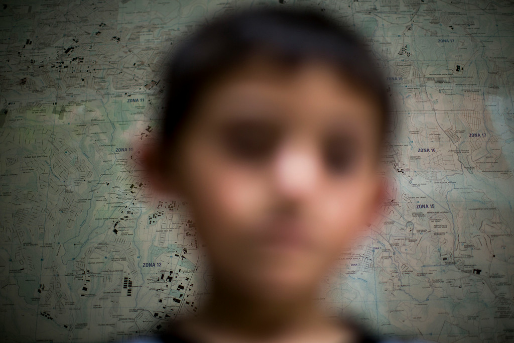 . In this June 19, 2014 photo, a Guatemalan child deported from the United State poses for photo in front of a map of the Guatemala City at an immigration shelter in Guatemala City. The number of unaccompanied minors detained on the U.S. border has more than tripled since 2011. Children are also widely believed to be crossing with their parents in rising numbers, although the Obama administration has not released year-by-year figures. (AP Photo/Luis Soto)