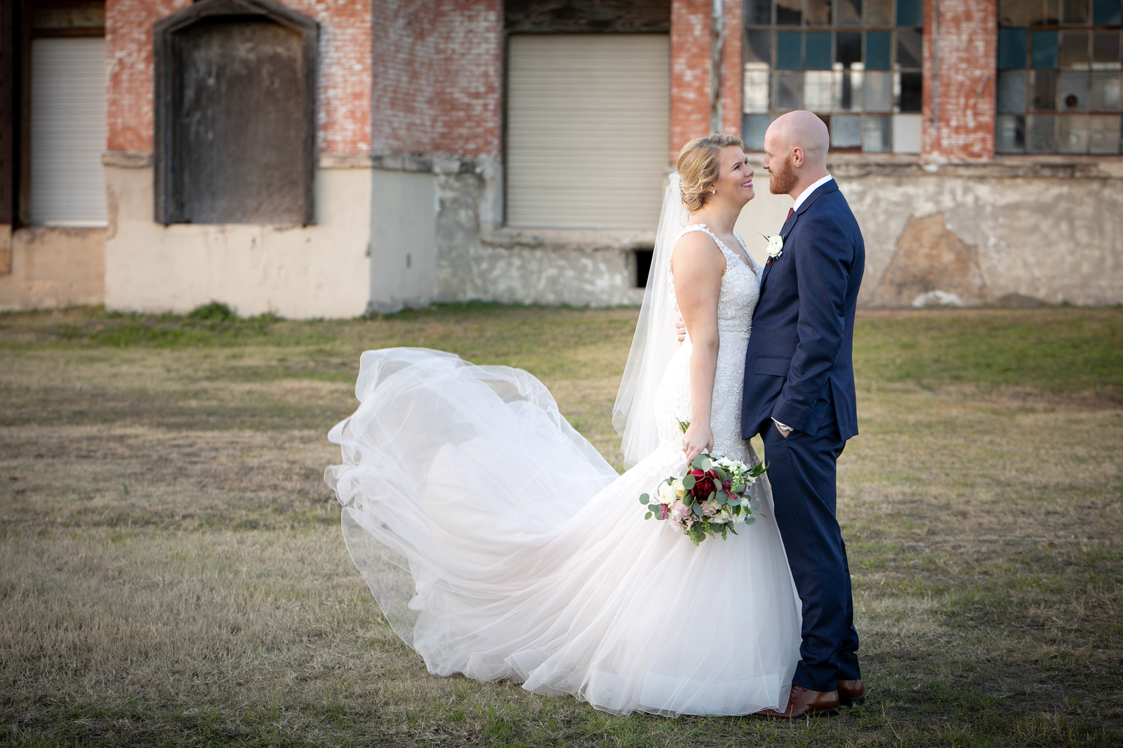 newlywed couple standing in front of a warehouse looking at each other