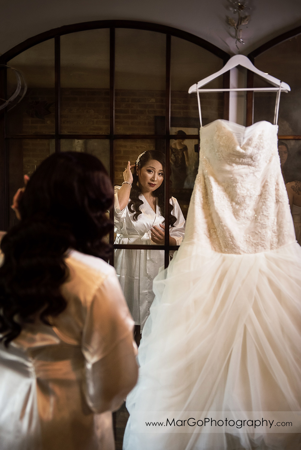 bride getting ready in front of the mirror at Sunol's Casa Bella