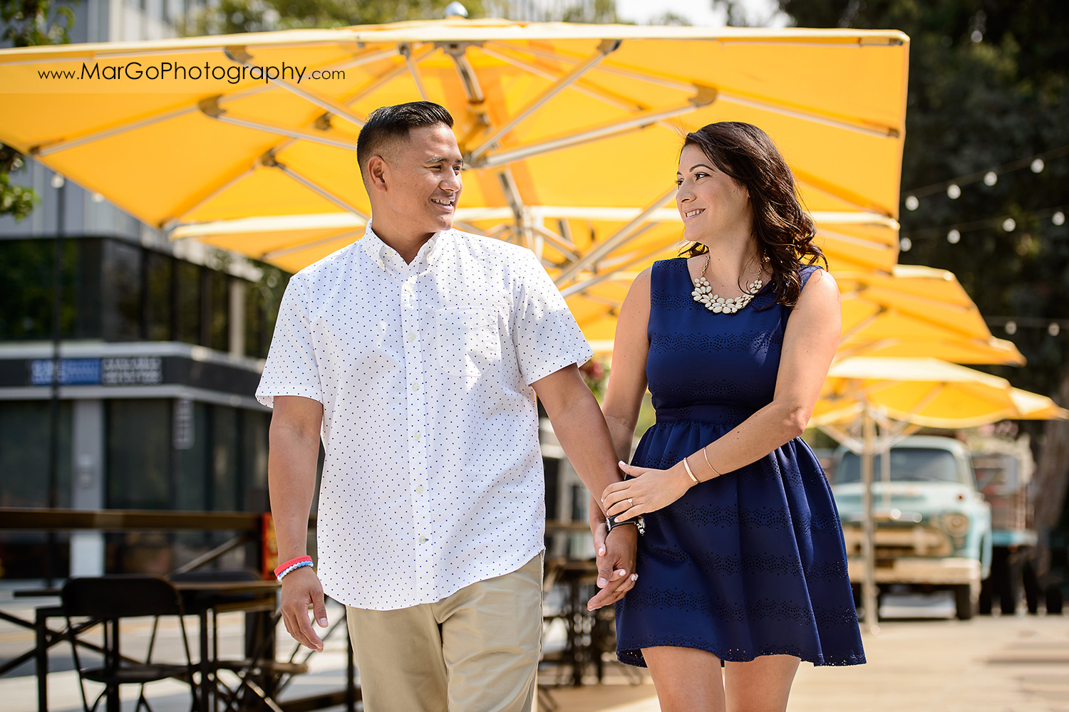 woman in blue dress and man in white shirt holding hands and walking with yellow umbrellas in background during engagement session at San Pedro Square Market in San Jose