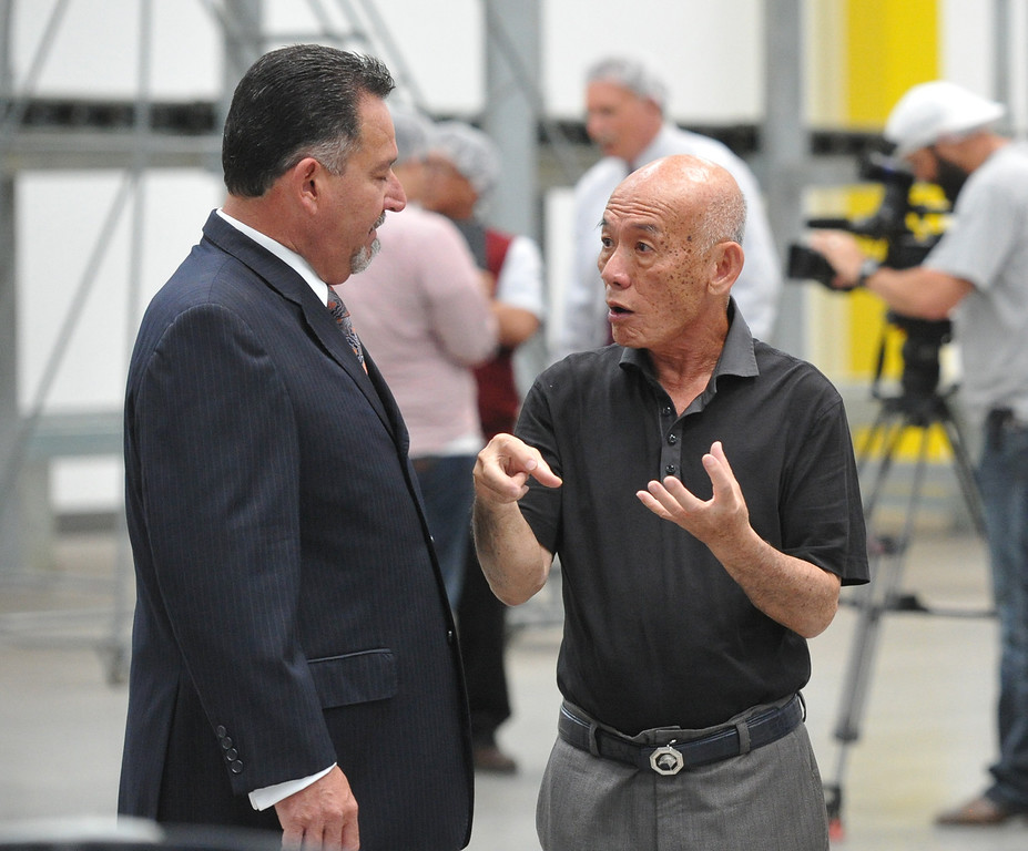. Irwindale Mayor Mark Breceda, left, talks with Huy Fong Foods CEO David Tran while on tour of the plant on Tuesday May 27, 2014. A team from Governor Jerry Brown�s Office of Business and Economic Development joins the tour of the 650,000 square-foot facility that the council voted has created a public nuisance. (Photo by Keith Durflinger/Whittier Daily News)
