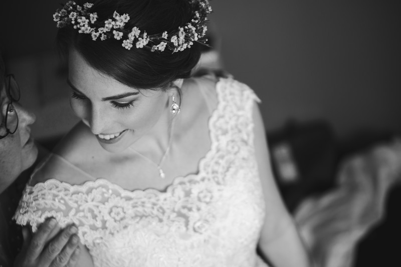 Bride smiling as her mother whispers into her ear.