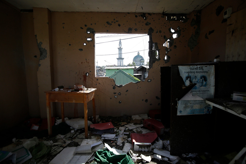 . The Saduc Grand Mosque, the biggest mosque that reopened near the former battle area between troops and Islamic extremists, is seen through a bullet-riddled wall as survivors gather for Eid al-fitr to mark the end of the holy fasting month of Ramadan in Marawi city, southern Philippines, Friday, June 15, 2018. Thousands of displaced residents celebrated Eid al-Fitr inside emergency shelters and the threat of Islamic extremists and unexploded bombs lingers in the rubble after a disastrous five-month siege by Islamic State group-aligned fighters that began more than a year ago. (AP Photo/Aaron Favila)