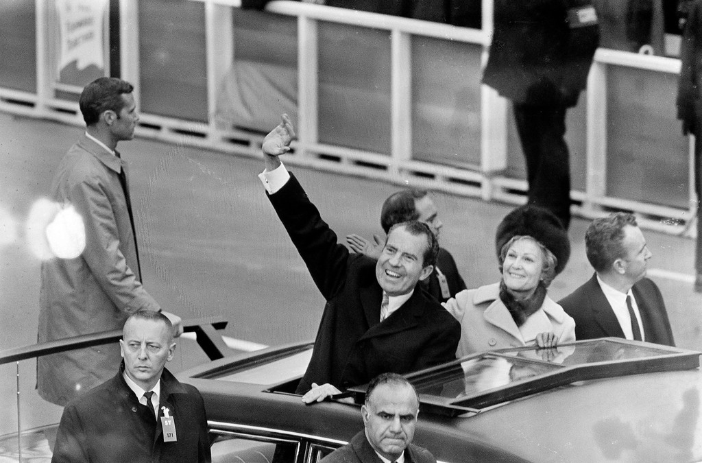 . President Nixon waves as he and First Lady Pat Nixon stand in the limousine carrying them from the inauguration at the Capitol to the White House in Washington, D.C., Jan. 20, 1969. Secret Service agents are seen alongside the car. (AP Photo)