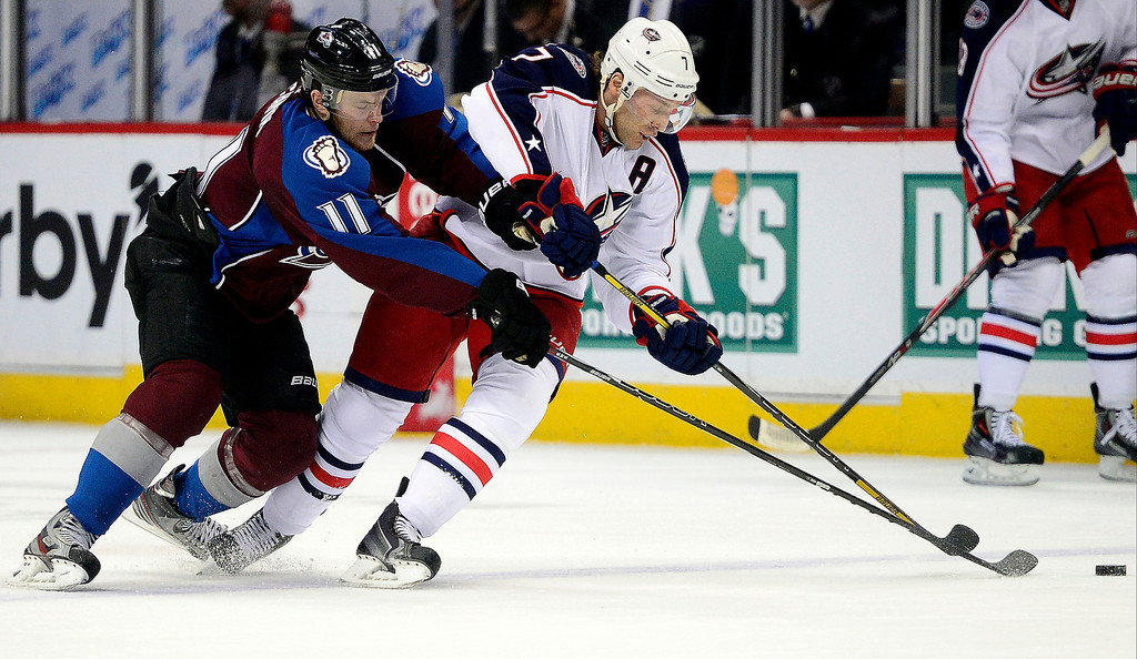 . Jamie McGinn (11) of the Colorado Avalanche pressures Jack Johnson (7) of the Columbus Blue Jackets during the first period. The Colorado Avalanche hosted the Columbus Blue Jackets at the Pepsi Center on Tuesday, December 31, 2013. (Photo by AAron Ontiveroz/The Denver Post)