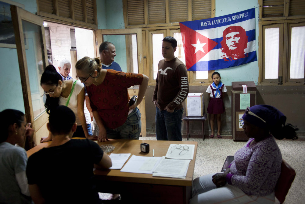 ". People are registered to vote at a polling station during parliament elections in Havana, Cuba, Sunday, Feb. 3, 2013. More than 8 million islanders are eligible to vote and will approve 612 members of the National Assembly and over 1,600 provincial delegates. On top, a Cuban flag with an image of the Argentinean born Cuban revolution leader Ernesto ""Che\"" Guevara. (AP Photo/Ramon Espinosa)"