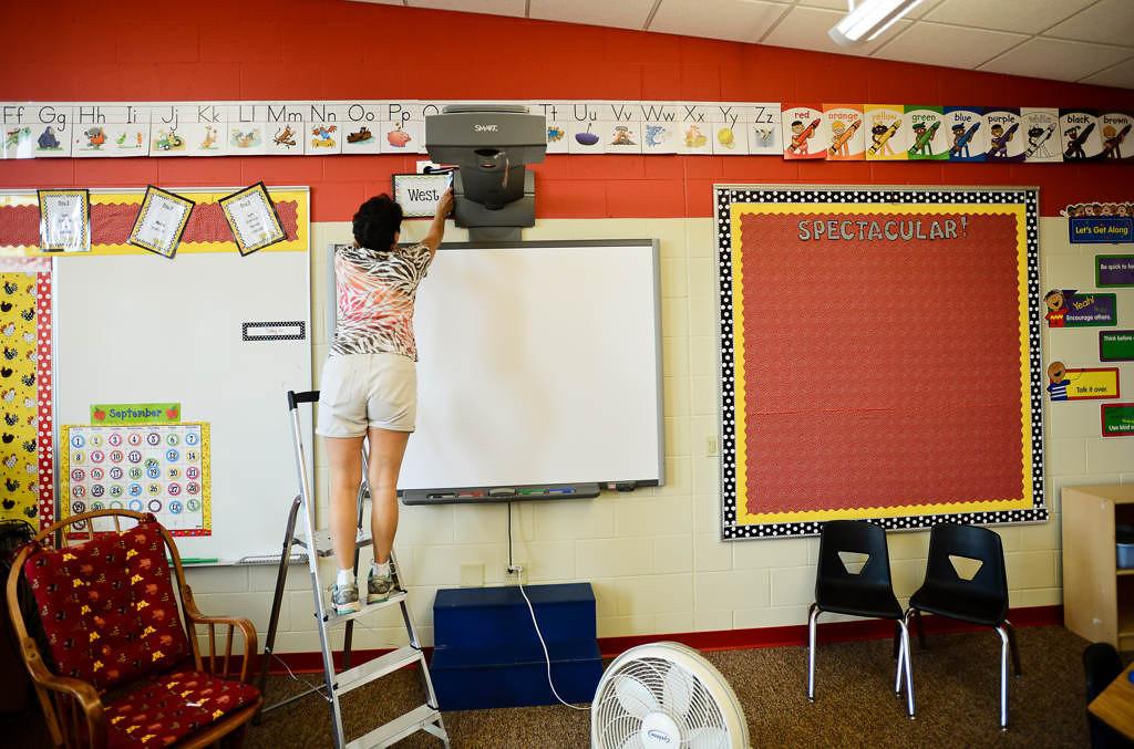 . Second-grade teacher Stacy Fesser puts up a sign for \'west\' in her new classroom at Wildwood.  (Pioneer Press: Ben Garvin)