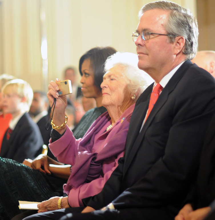 . Former First Lady Barbara Bush (C) takes pictures with her son former Florida governor Jeb Bush and First Lady Michelle Obama (L) as her husband former US president George Bush is awarded the Medal of Freedom on Feburary 15, 2011 at the White House in Washington.        (TIM SLOAN/AFP/Getty Images)