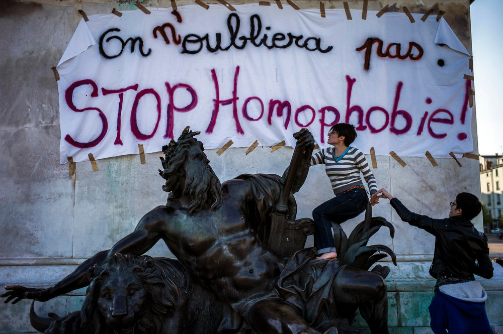 """. A supporter of same sex marriage climbs on a statue on April 23, 2013 in Lyon, southeastern France, some hours after the French National Assembly adopted a bill legalizing same-sex marriages and adoptions for gay couples, defying months of opposition protests. In its second and final reading, a majority of lawmakers approved the bill by a vote of 331 to 225. The banner reads : We will not forget, stop homophobia !\"""". JEFF PACHOUD/AFP/Getty Images"""
