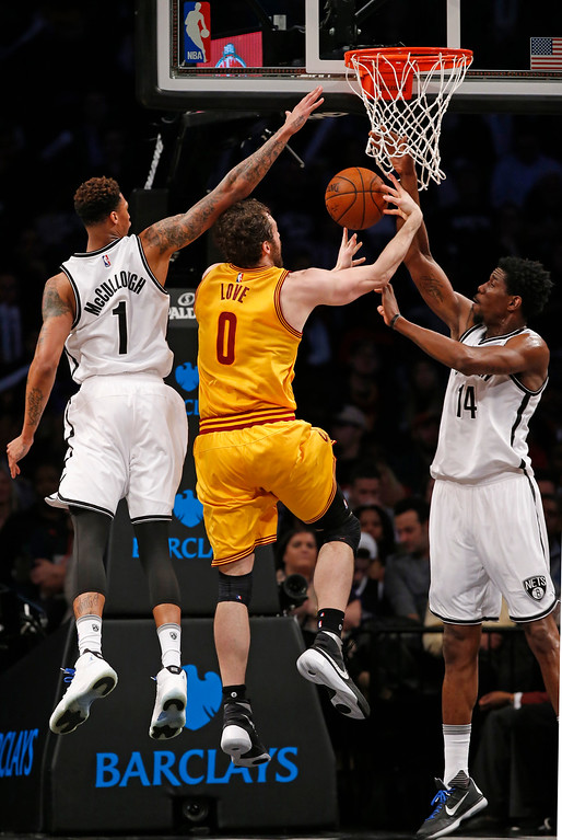 . Brooklyn Nets forward Chris McCullough (1) and Brooklyn Nets center Henry Sims (14) defend Cleveland Cavaliers forward Kevin Love (0) in the second half of an NBA basketball game, Thursday, March 24, 2016, in New York. The Nets beat the Cavaliers 104-95. (AP Photo/Kathy Willens)