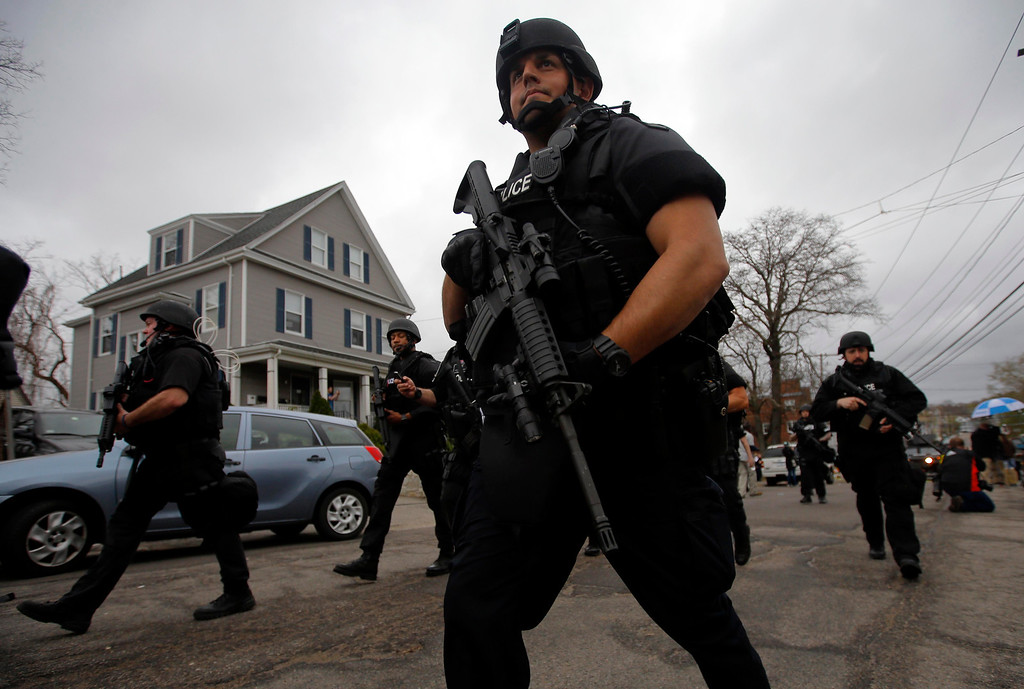 . Police officers search house to house for the second suspect in the Boston Marathon bombings in a neighborhood of Watertown, Massachusetts April 19, 2013.  Black Hawk helicopters and heavily armed police descended on a Boston suburb Friday in a massive search for an ethnic Chechen suspected in the Boston Marathon bombings, hours after his brother was killed by police in a late-night shootout.     REUTERS/Brian Snyder