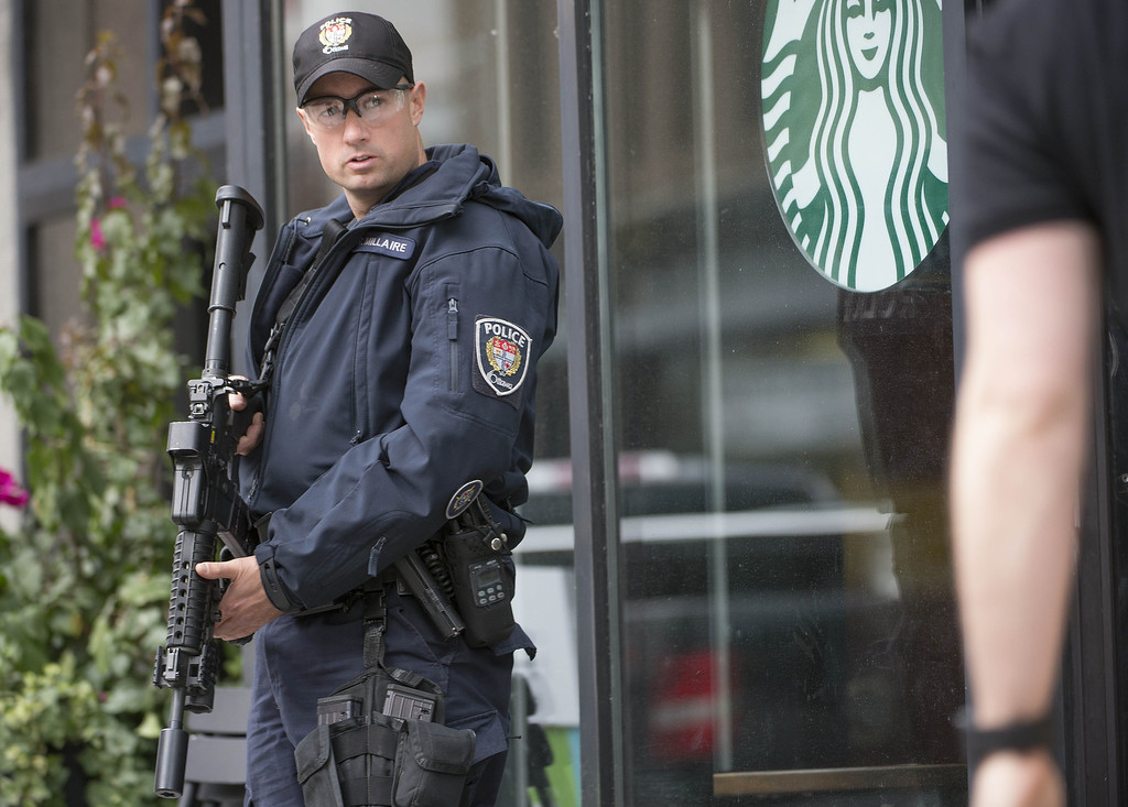. An police officer stands watch outside a Starbucks in Ottawa,Ontario after multiple shootings on October 22, 2014. AFP PHOTO/Peter McCabe/AFP/Getty Images