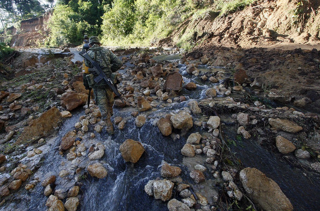 . Mexican soldiers walk along a damaged road to bring relief aid to La Pintada, state of Guerrero, Mexico, on September 19, 2013 as heavy rains hit the country. AFP PHOTO/Pedro PARDO/AFP/Getty Images
