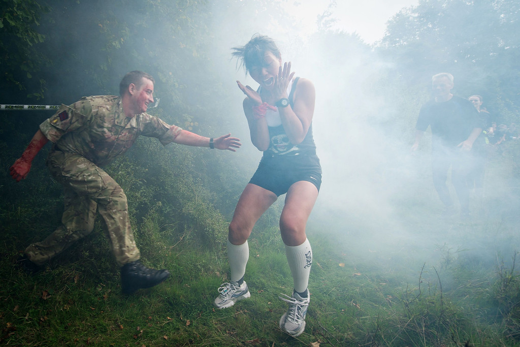 """. A participant is terrified by a \""""zombie\"""" soldier in a forest section during one of Britain\'s biggest horror events, the \""""Zombie Evacuation Race\"""" at Carver Barracks near Saffron Walden, England, on October 5, 2013. The race sees thousands of participants attempt to complete a gruelling 5 kilometre cross-country run, while evading \""""zombies\"""", intent on snatching the three life-line strips hanging from every runner\'s waist.  Those who manage to get through with any strips remaining are named as survivors while those without take home an \""""infected\"""" badge. LEON NEAL/AFP/Getty Images"""