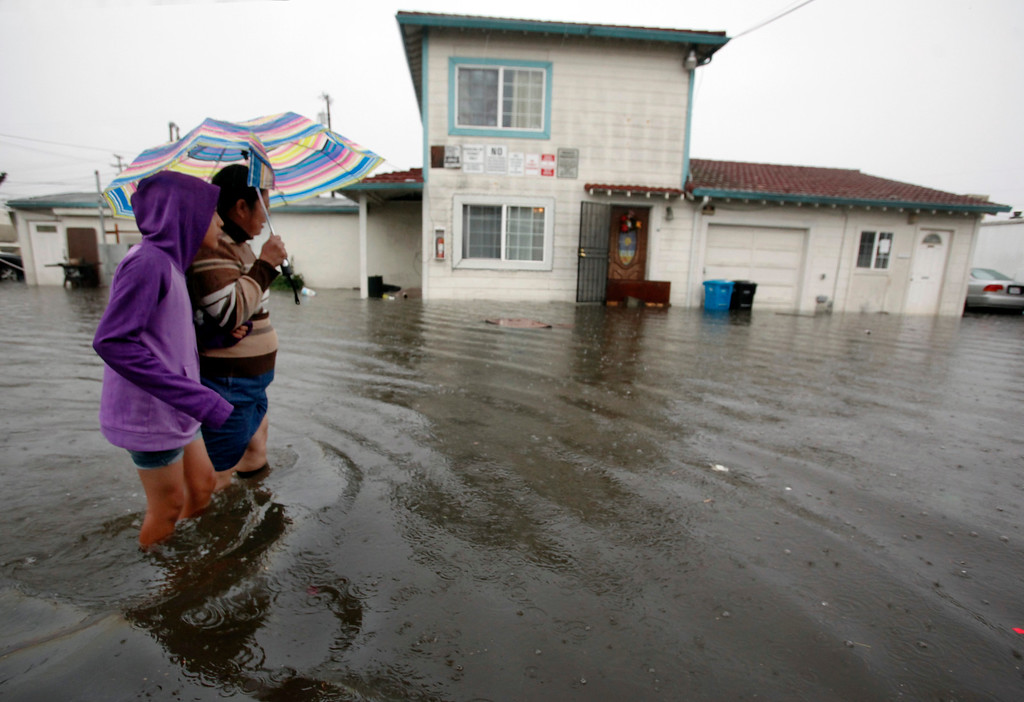 . Jessica Avila and Socorro walk slowly through the flooded Le Mar Trailer Park in Redwood City, Calif., during a visit to friends Thursday afternoon, Dec. 11, 2014. (Karl Mondon/Bay Area News Group)