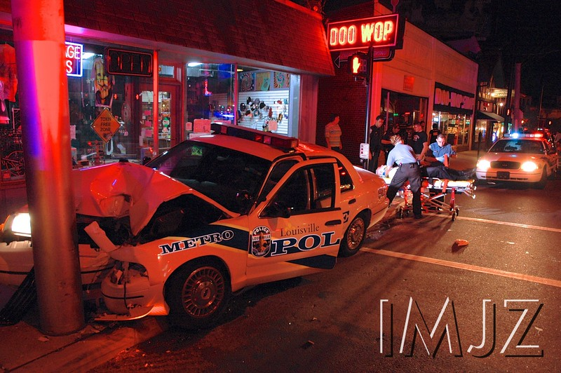 A Louisville Metro Police officer is carried away on a gurney by EMTs following a single car accident on Bardstown Road. August 21st, 2008.