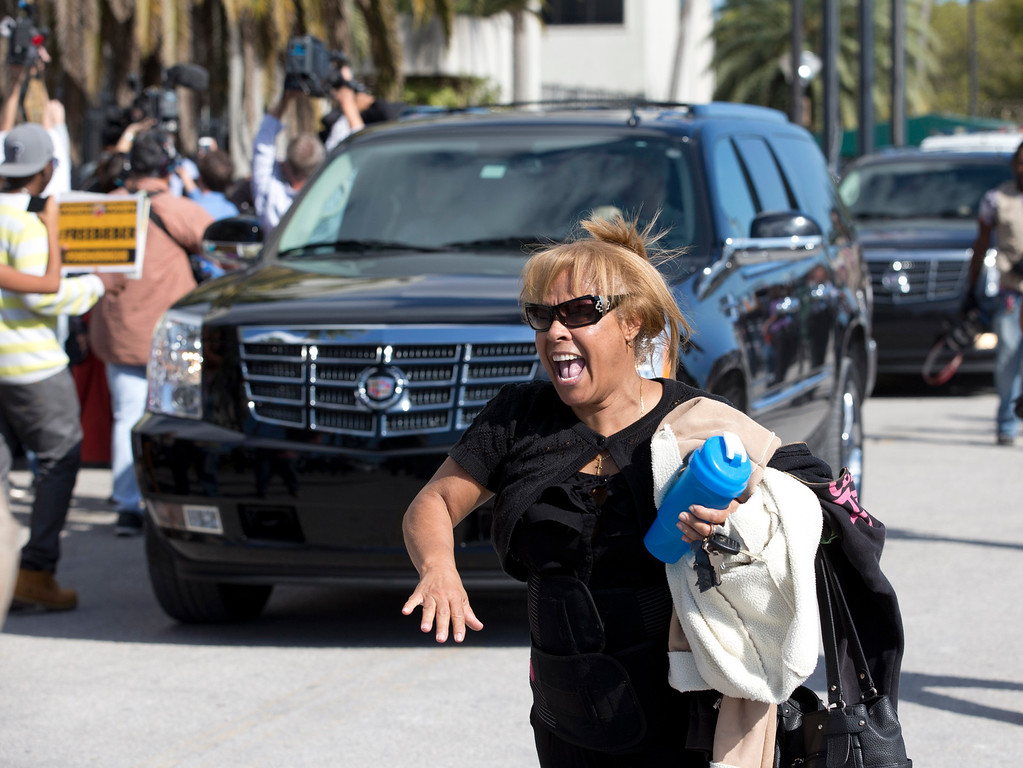 . An unidentified fan screams as the motorcade carrying pop singer Justin Bieber leaves the Turner Guilford Knight Correctional Center, Thursday Jan. 23, 2014 in Doral, Fla. Bieber was arrested earlier in the day in Miami Beach on charges including driving under the influence and resisting arrest. He was arrested after police said they saw him speeding down a residential street in Miami Beach in a yellow Lamborghini. Officers say he had an expired license, was initially not cooperative when he was pulled over and smelled of alcohol. (AP Photo/Wilfredo Lee)