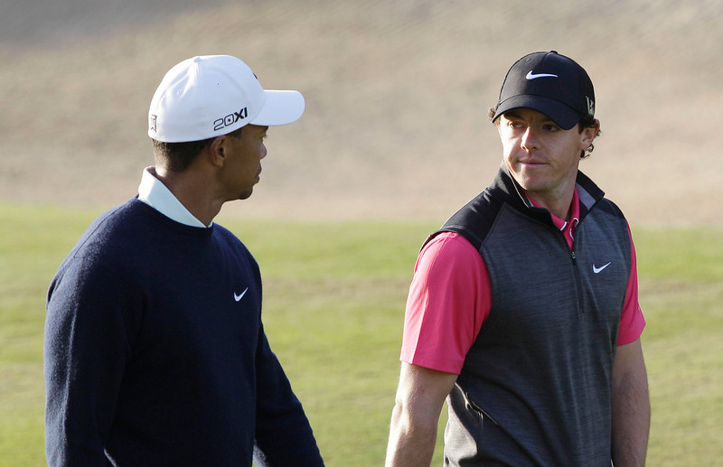 . Rory McIlroy from Northern Ireland, rear, and Tiger Woods from U.S. talk on the 13th hole during the first round of Abu Dhabi Golf Championship in Abu Dhabi, United Arab Emirates, Thursday, Jan. 17, 2013. (AP Photo/Kamran Jebreili)