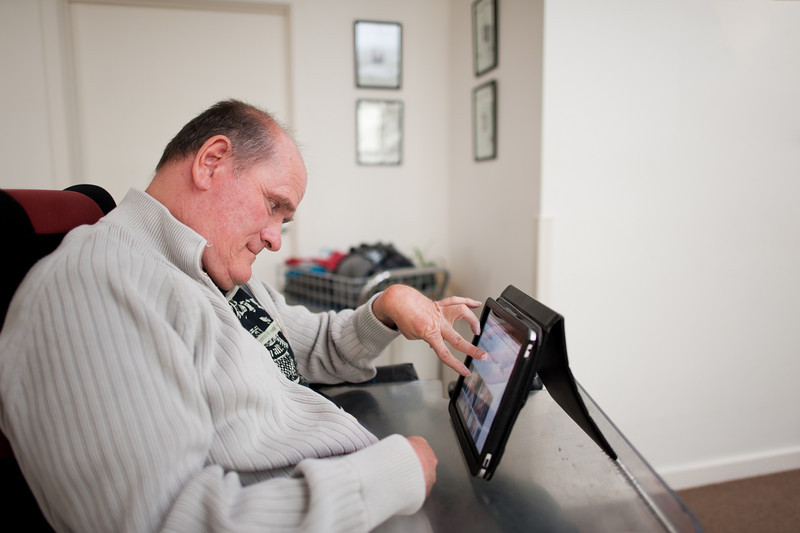 Fifty-five year old man with a disability using computer inside his home
