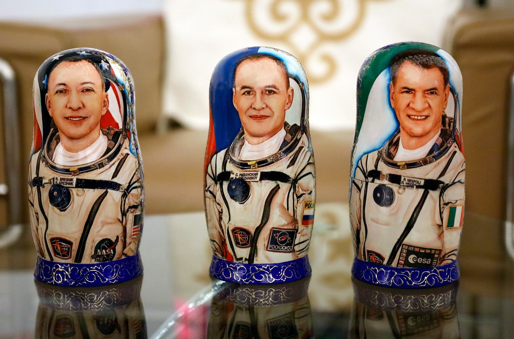 . Matryoshka, Russian traditional wooden dolls, decorated with portraits of U.S. astronaut Randy Bresnik, left, Russian cosmonaut Sergey Ryazanskiy, center, and Italian astronaut Paolo Nespoli are displayed during a welcome ceremony at the airport of Karaganda, Kazakhstan, Thursday, Dec. 14, 2017. Three astronauts on Thursday landed back on Earth after nearly six months aboard the International Space Station. (AP Photo/Dmitri Lovetsky, Pool)