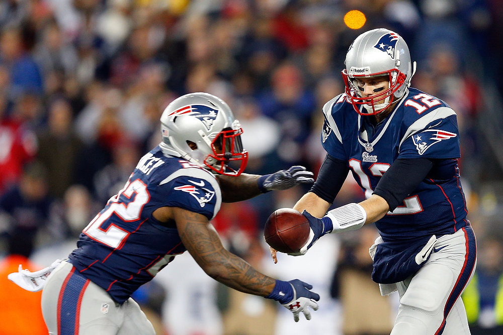 Description of . Tom Brady #12 of the New England Patriots hands the ball off to Stevan Ridley #22 against the Houston Texans during the 2013 AFC Divisional Playoffs game at Gillette Stadium on January 13, 2013 in Foxboro, Massachusetts.  (Photo by Jim Rogash/Getty Images)