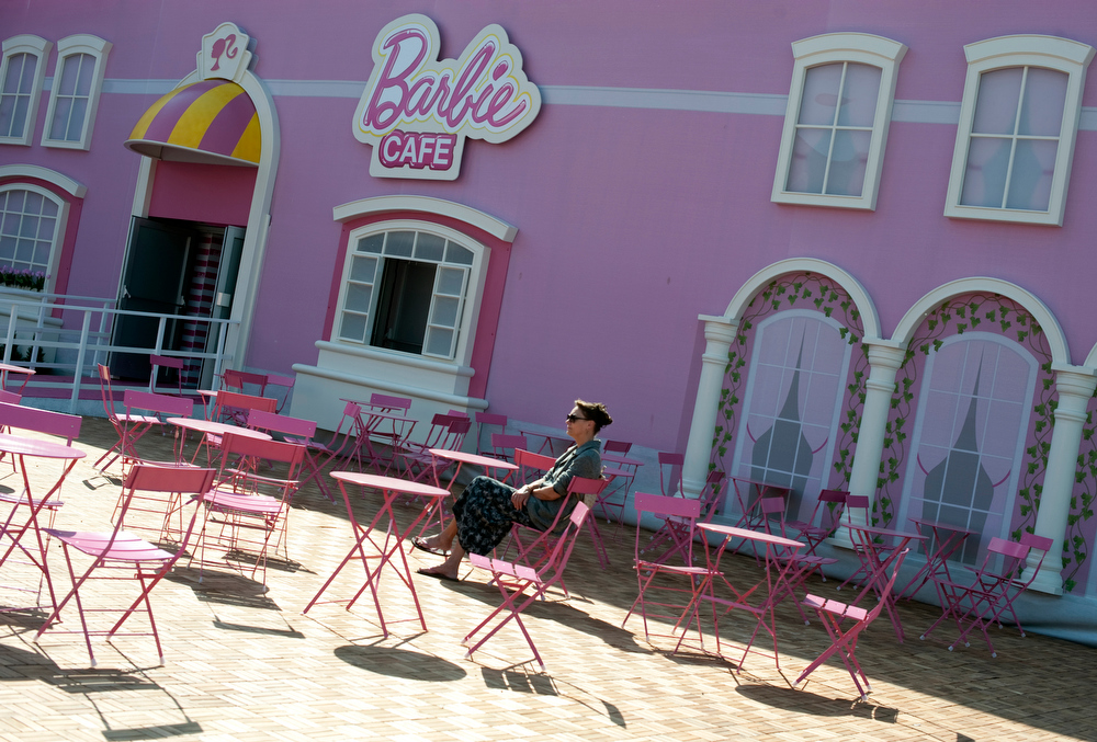 . A woman sits on the terrace of the Barbie Cafe in front of the Barbie Dreamhouse - the first life-sized giant mansion dedicated to the doll in Europe, ahead of its opening near the Alexanderplatz in Berlin on May 16, 2013.  BARBARA SAX/AFP/Getty Images