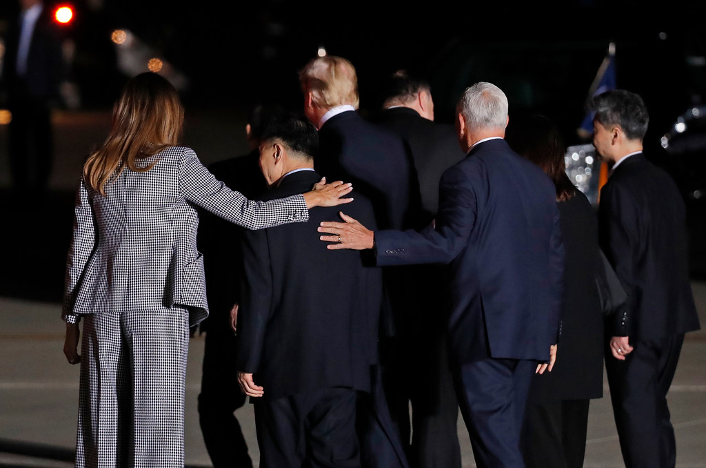 . First lady Melania Trump and Vice President Mike Pence put their arms around North Korean detainee Tony Kim as they walk with President Donald Trump, Secretary of State Mike Pompeo, Kim Dong Chul, and Kim Hak Song as they were leaving from Andrews Air Force Base, Md., Thursday, May 10, 2018. (AP Photo/Alex Brandon)