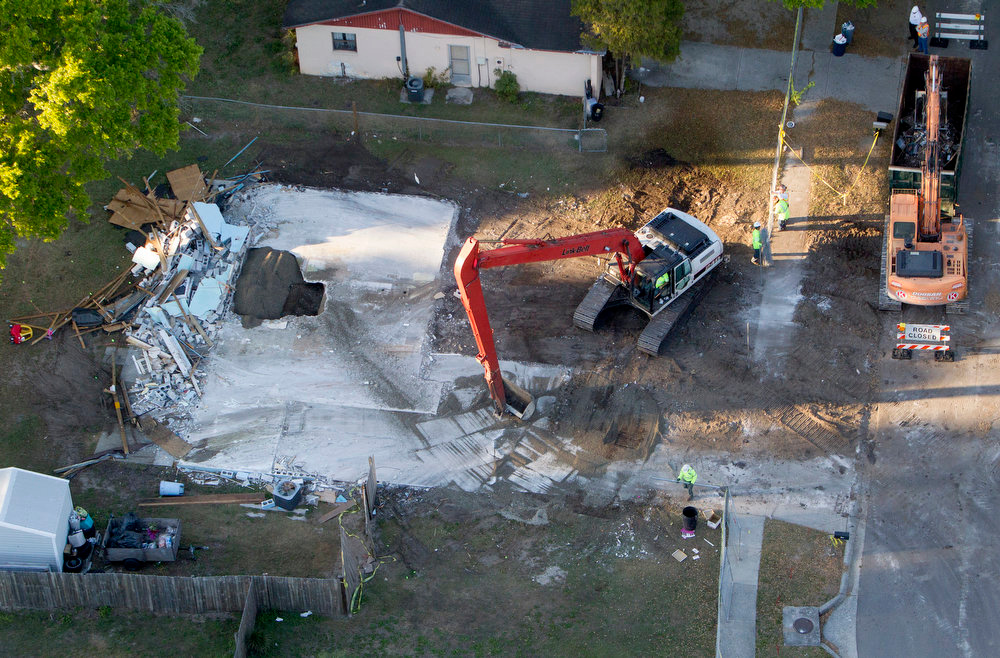 . This aerial photo shows demolition workers picking up the remnants from the home of Jeff Bush, Tuesday, March 5, 2013, in Seffner, Fla.  A huge sinkhole opened up under a bedroom in the home last Thursday, Feb. 28,  and swallowed Jeff Bush, 37. Officials gave up hope of finding Bush alive and filled in the hole with crushed rock.  (AP Photo/The Tampa Bay Times, Dirk Shadd)