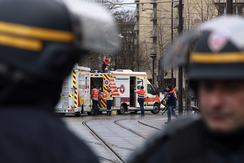 . Members of the French riot police (CRS) stand next to disaster and emergency services vans near Porte de Vincennes in Paris on January 9, 2015, after at least one person was injured when a gunman opened fire at a kosher grocery store and took at least five people hostage, sources told AFP. The attacker was suspected of being the same gunman who killed a policewoman in a shooting in Montrouge in southern Paris on January 8. AFP PHOTO / LOIC  VENANCE/AFP/Getty Images