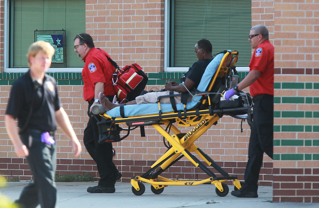. Emergency personnel remove a person from the school after at least one person was killed and others were injured during an altercation inside Spring High School Wednesday, Sept. 4, 2013, morning in Spring, Texas.(AP Photo/The Houston Chronicle, Mayra Beltran )