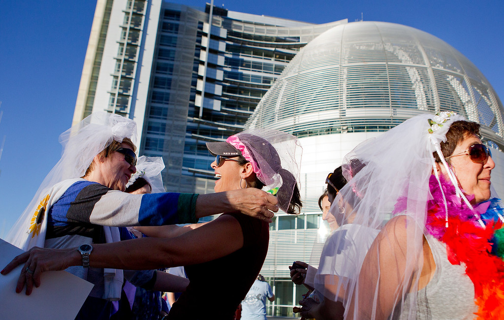 . From left, Cassie Will-Darnall and Geri Ledvina hug at a San Jose City Hall rally to celebrate the U.S. Supreme Court decision on DOMA and Proposition 8, in San Jose, Calif. on Wednesday, June 26, 2013.  At right is Michelle Raiche. (LiPo Ching/Bay Area News Group)