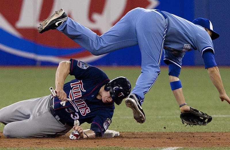 . The Toronto Blue Jays\' John McDonald,right,  collides with the Twins\' Justin Morneau at second base after Twins\' Michael Cuddyer grounds into fielder\'s choice during eight inning Wednesday, July 7, 2010. (The Canadian Press,Chris Young)