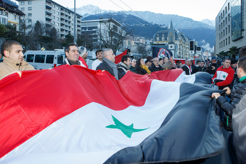 . Demonstrators support Syrian President Bashar  Assad as they protest near the venue of the of the Geneva II peace talks, an international conference aimed at ending the country\'s brutal conflict,  in Montreux, Switzerland, Wednesday, Jan. 22, 2014.  (AP Photo/Keystone, Salvatore Di Nolfi)