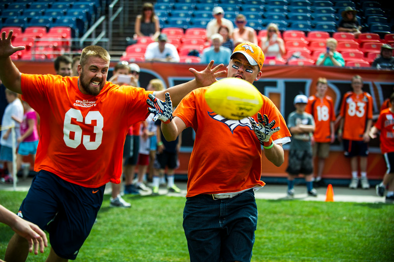 . Ben Garland #63 of the Denver Broncos sneaks up Michael Aragon, 28, of Denver, as he tries to tell in a short pass during the National Sports Center for the Disabled\'s Denver Broncos Ability Clinic at Sports Authority Field at Mile High on Tuesday, July 08, 2014 in Denver, CO.   (Photo by Kent Nishimura/The Denver Post)