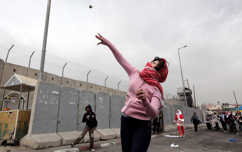 . A Palestinian woman throws a stone towards Israeli troops at Qalandia checkpoint between Jerusalem and the West Bank city of Ramallah, Saturday, March 8, 2014. Palestinian women marked International Women\'s Day by marching to the checkpoint where clashes broke out with Israeli troops. (AP Photo/Majdi Mohammed)