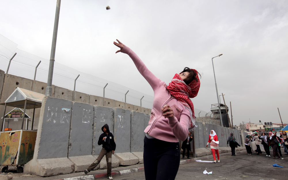 Description of . A Palestinian woman throws a stone towards Israeli troops at Qalandia checkpoint between Jerusalem and the West Bank city of Ramallah, Saturday, March 8, 2014. Palestinian women marked International Women's Day by marching to the checkpoint where clashes broke out with Israeli troops. (AP Photo/Majdi Mohammed)
