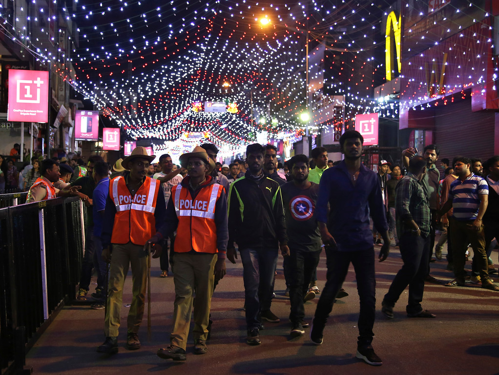 . Indian policemen walk alongside revelers as they arrive for New Year\'s celebrations in Bangalore, India, Sunday, Dec. 31, 2017. Security was tight in the southern Indian city of Bangalore to prevent a repeat of incidents of alleged groping and molestation of several women during last year\'s New Year\'s Eve celebrations. (AP Photo/Aijaz Rahi)