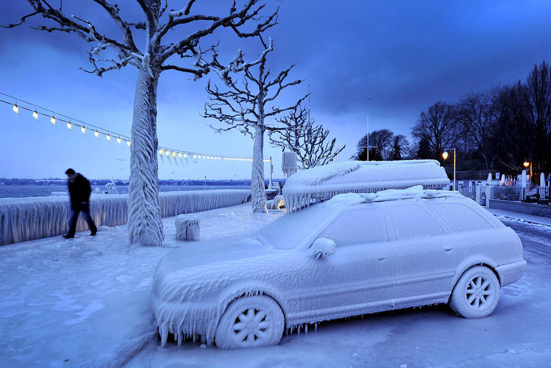 . A man walks past an ice covered car on the frozen waterside promenade at Lake Geneva in the city Versoix, near Geneva on early February 5, 2012. The death toll from the vicious cold snap across Europe has risen to more than 260, with the winter misery set to hit thousands of those seeking to escape it as air traffic was hit.    AFP PHOTO / FABRICE  COFFRINI/AFP/Getty Images