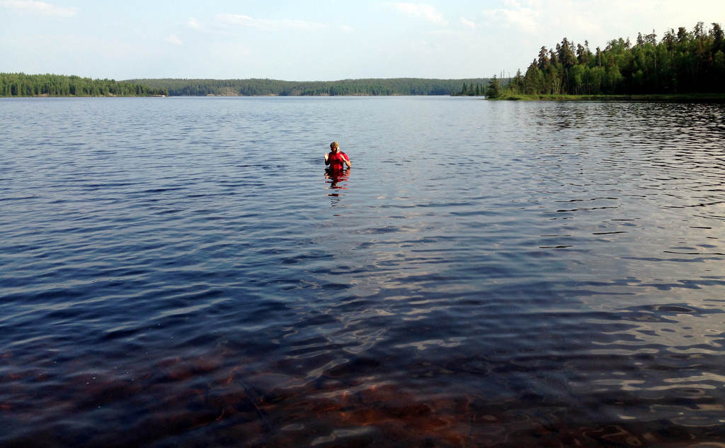 . Steve Safranski of Eden Prairie, Minn., swats at head-buzzing flies during a swim  in early July 2013 inside Woodland Caribou Provincial Park in Ontario, Canada.