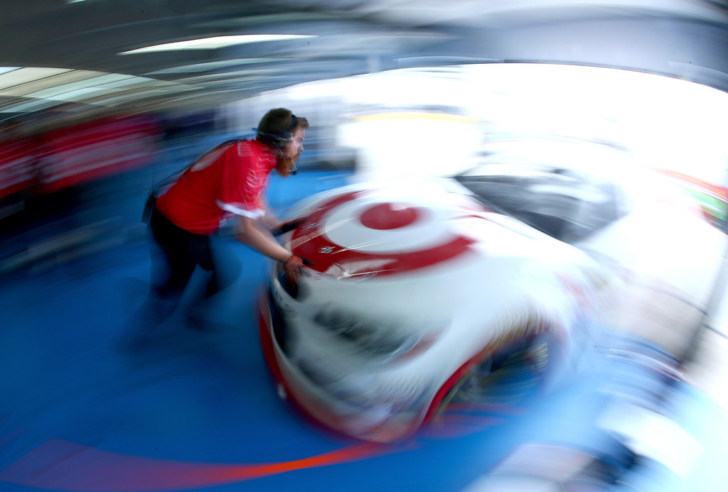 . CONCORD, NC - OCTOBER 11:  A crew member pushes the #51 Target Chevrolet, driven by Kyle Larson, out of the garage during practice for the NASCAR Sprint Cup Series Bank of America 500 at Charlotte Motor Speedway on October 11, 2013 in Concord, North Carolina.  (Photo by Jonathan Ferrey/Getty Images)